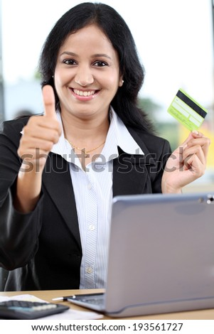 Happy young businesswoman holding credit card and showing thumbs up gesture - stock photo