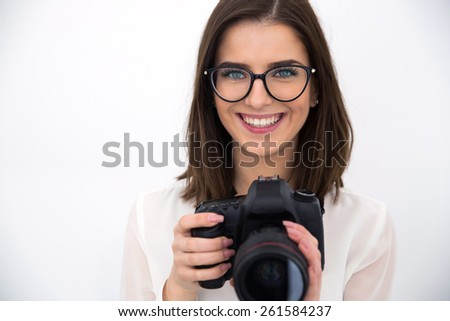 Happy young businesswoman in glasses holding camera - stock photo