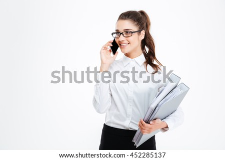 Happy young businesswoman in glasses holding folders and talking on mobile phone over white background - stock photo