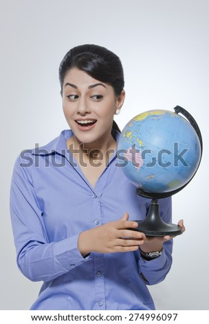 Happy young businesswoman looking at globe against gray background - stock photo