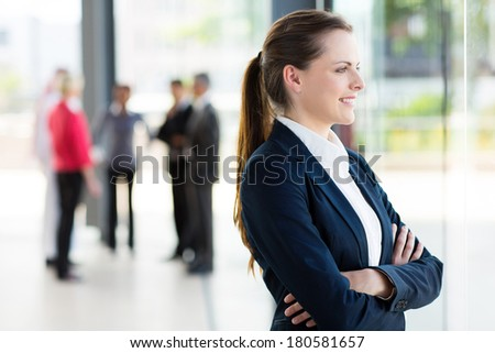 happy young businesswoman looking outside office window - stock photo