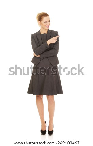 Happy young businesswoman pointing aside. - stock photo