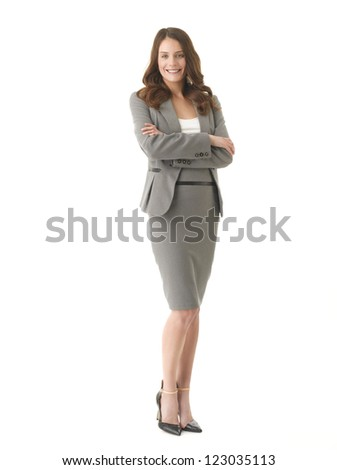 Happy young businesswoman with arms crossed standing against isolated white background - stock photo
