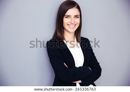 Happy young businesswoman with arms folded standing over gray background. Looking at camera - stock photo