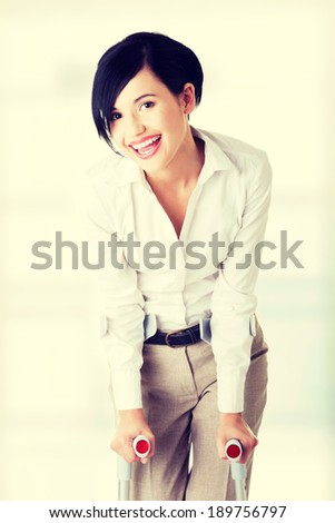 Happy young businesswoman with crutches. Disabled person in work. - stock photo