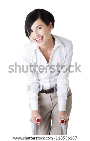 Happy young businesswoman with crutches, isolated on white. Disabled person in work. - stock photo