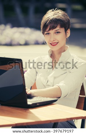 Happy young businesswoman with laptop at sidewalk cafe - stock photo