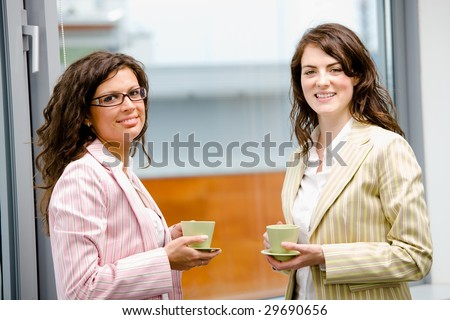 Happy young businesswomen having break at office drinking coffee, looking at camera, smiling. - stock photo