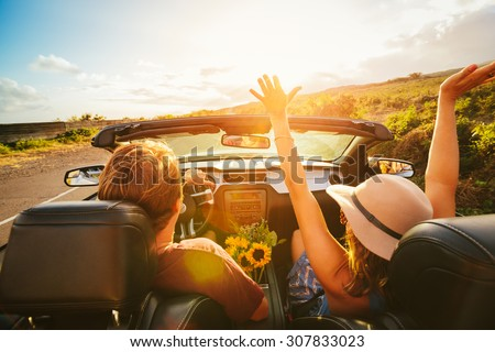 Happy Young Carefree Couple Driving Along Country Road in Convertible at Sunset - stock photo