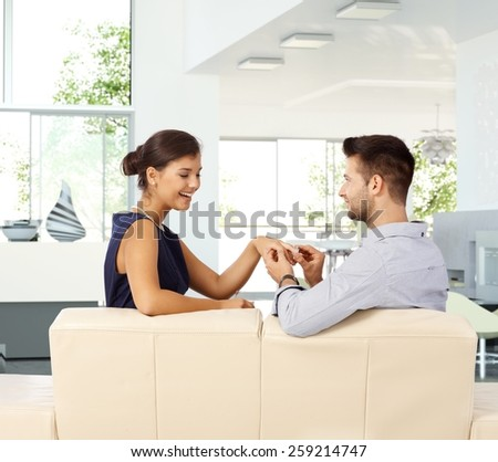 Happy young casual attractive caucasian lady is getting engagement ring from boyfriend at home. Sitting on sofa ring on hand, smiling, proposal, bright home. - stock photo