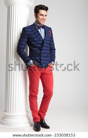 Happy young casual man smiling while looking away with his hands in pockets. - stock photo