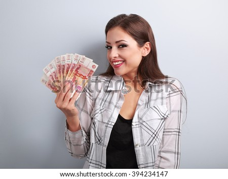 Happy young casual woman holding rubles with toothy smiling on blue background - stock photo