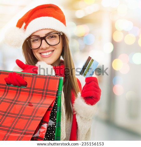 Happy young Caucasian brunette woman with Christmas hat shopping at the mall holding credit card and shopping bags. Smiling Santa Claus girl buying presents at shopping center. - stock photo
