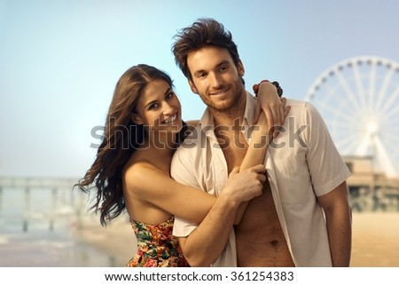 Happy young caucasian couple at sandy summer holiday beach. Smiling looking at camera, copyspace. Handsome bristly man. - stock photo