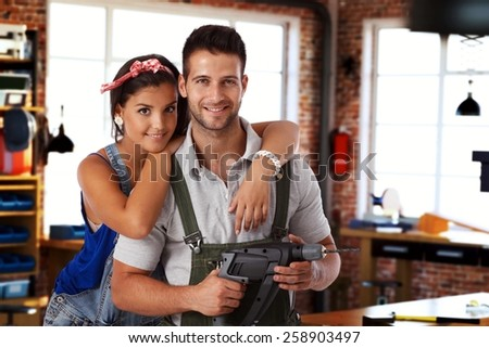 Happy young caucasian couple standing at home workshop, looking at camera, hugging, smiling. Power drill in hand. - stock photo