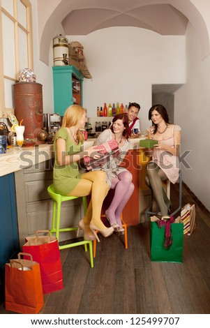 happy young caucasian girls sitting on colorful chairs agaisnt the counter in a cafe exchanging gifts surounded with shopping bags - stock photo