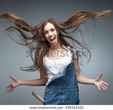 happy young caucasian woman in worker suit holding painting roll - stock photo