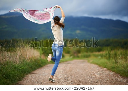 Happy young caucasian woman outdoor on a rural dirt road in the countryside dancing - stock photo