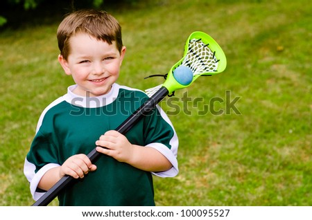 Happy young child lacrosse player with his stick - stock photo