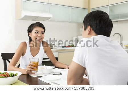 Happy young Chinese couple eating at home in the kitchen - stock photo