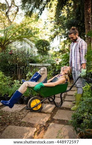 Happy young colleagues enjoying with wheelbarrow in community garden - stock photo