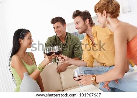 Happy young companionship clinking glasses, having fun, celebrating. - stock photo