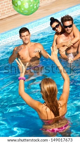 Happy young companionship having summer fun in swimming pool. - stock photo