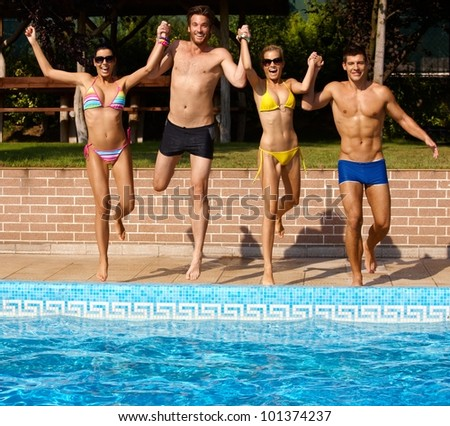 Happy young companionship jumping to outdoor swimming pool, having fun. - stock photo
