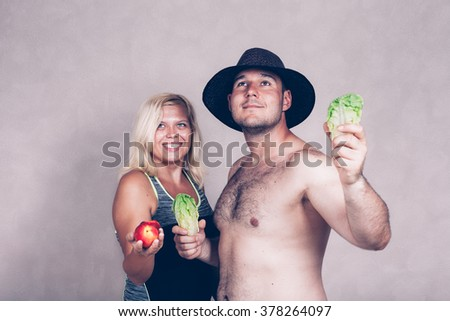 Happy young corpulent couple holding lettuce and nectarine. - stock photo