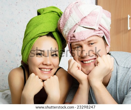 happy young couple after shower with towels on their heads - stock photo