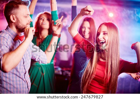 Happy young couple and their friends on background dancing together in night club - stock photo