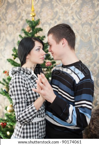 Happy young couple at Christmas. Happy young woman and man in domestic room on Christmas day. - stock photo