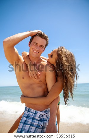 Happy young couple at the beach having fun. - stock photo