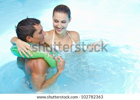 Happy young couple bathing with floating ring in swimming pool - stock photo