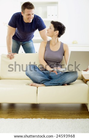 Happy young couple browsing internet on laptop computer at home, smiling. - stock photo