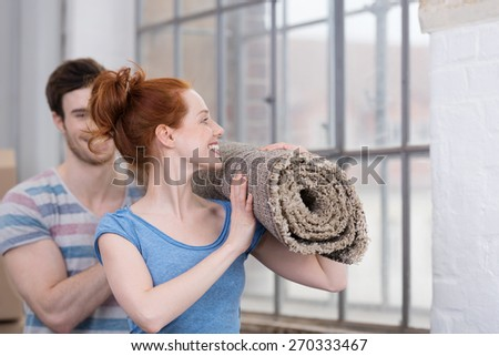 Happy young couple carrying a new carpet for their house laughing and smiling as they walk past a large window - stock photo