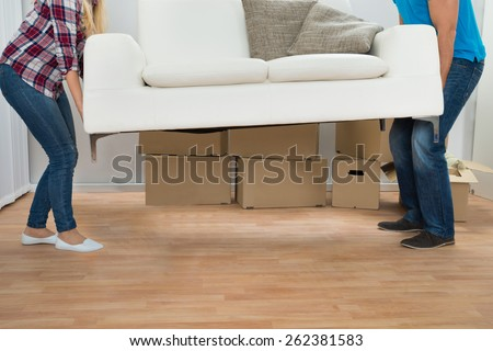 Happy Young Couple Carrying Couch In New Home - stock photo