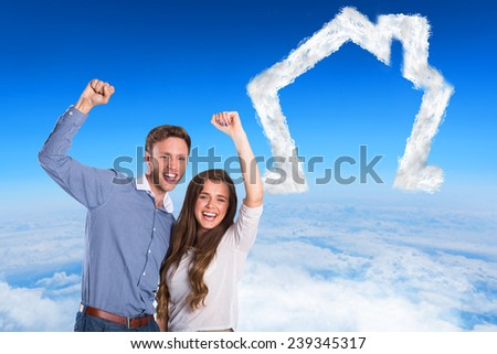 Happy young couple cheering against blue sky over white clouds - stock photo