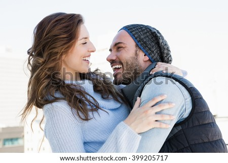 Happy young couple cuddling each other and smiling outdoors - stock photo
