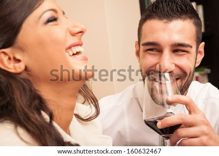 Happy young couple drinking a glass of wine. - stock photo