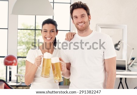 Happy young couple drinking beer at home, clinking glasses, looking at camera. - stock photo
