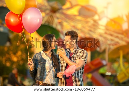 Happy young  couple eating cotton candy in amusement park - stock photo