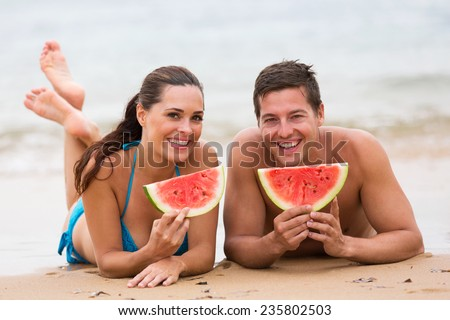 happy young couple eating watermelon on beach  - stock photo