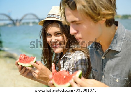 Happy young couple eating watermelon on the beach. Youth lifestyle. Happiness, joy, friendship, holiday, beach, summer concept. Group of young people having fun outdoor. - stock photo