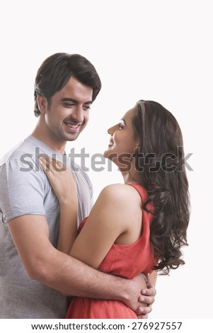 Happy young couple embracing against over background - stock photo