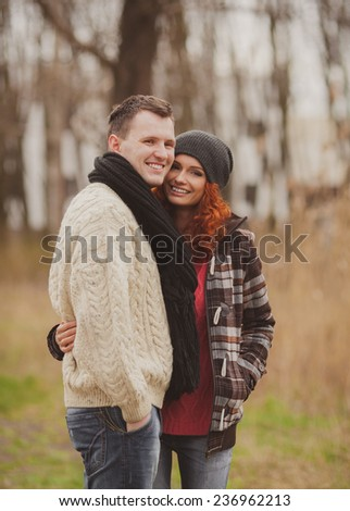 Happy young couple embracing and having fun together outdoors in autumn  - stock photo