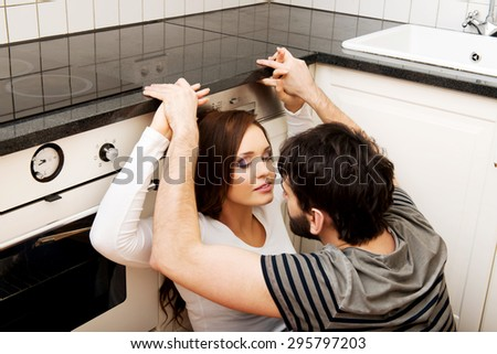 Happy young couple embracing each-other in the kitchen. - stock photo
