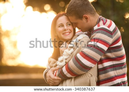 Happy young couple embracing while walking in a park on  a sunny autumn day - stock photo