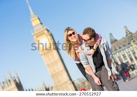 Happy young couple enjoying a piggyback ride in London with Big Ben amd Westminster palace on background. They are both wearing sunglasses and spring clothing. - stock photo