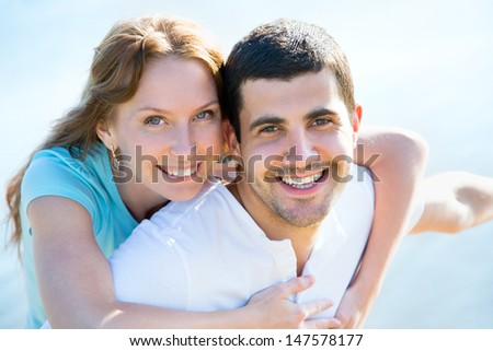Happy young couple enjoying a solitary beach  - stock photo